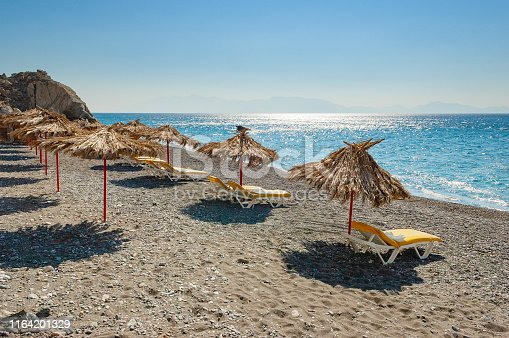 Empty sand and pebble beach with palm leaf umbrellas and lounge chairs by the sea on the Greek island of Kos. Vacation, summer and travel concepts.