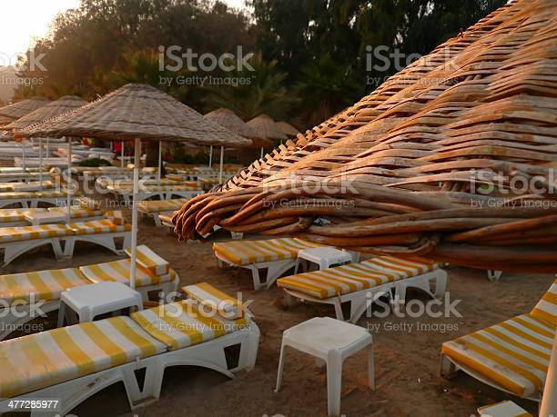 Photo of Empty beach with parasols and deck chairs