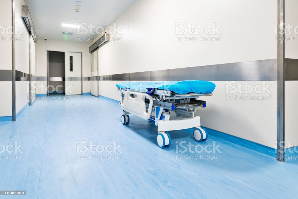Empty bed in hospital corridor.