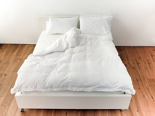Empty Bed With White Bedding stock photo
