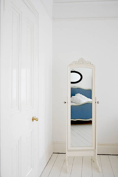 Empty bedroom with mirror and bed stock photo