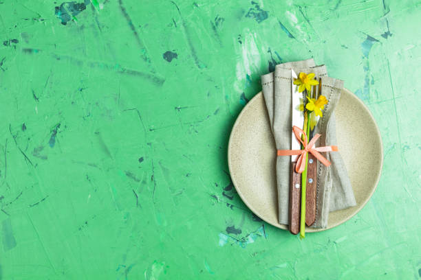Empty beige plate and cutlery with daffodils on a napkin stock photo