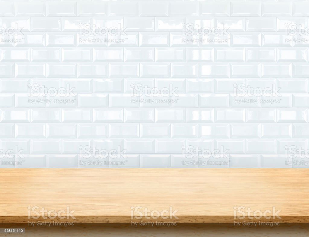 Empty beige wood table top with glossy white tile wall stock photo