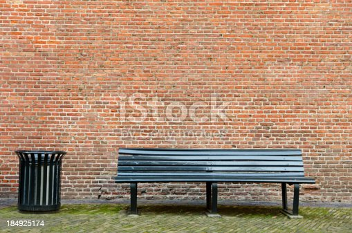 An empty bench and a garbage bin in front of a brick wall. Place your own object on the bench.See also