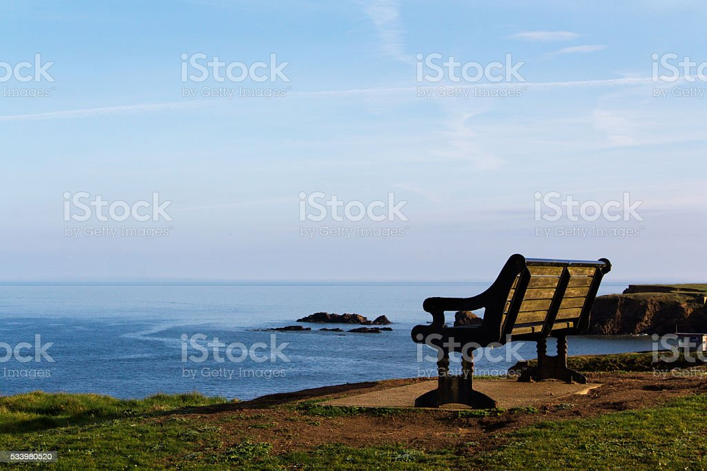 Empty bench over looking the coast in Bude, Cornwall stock photo