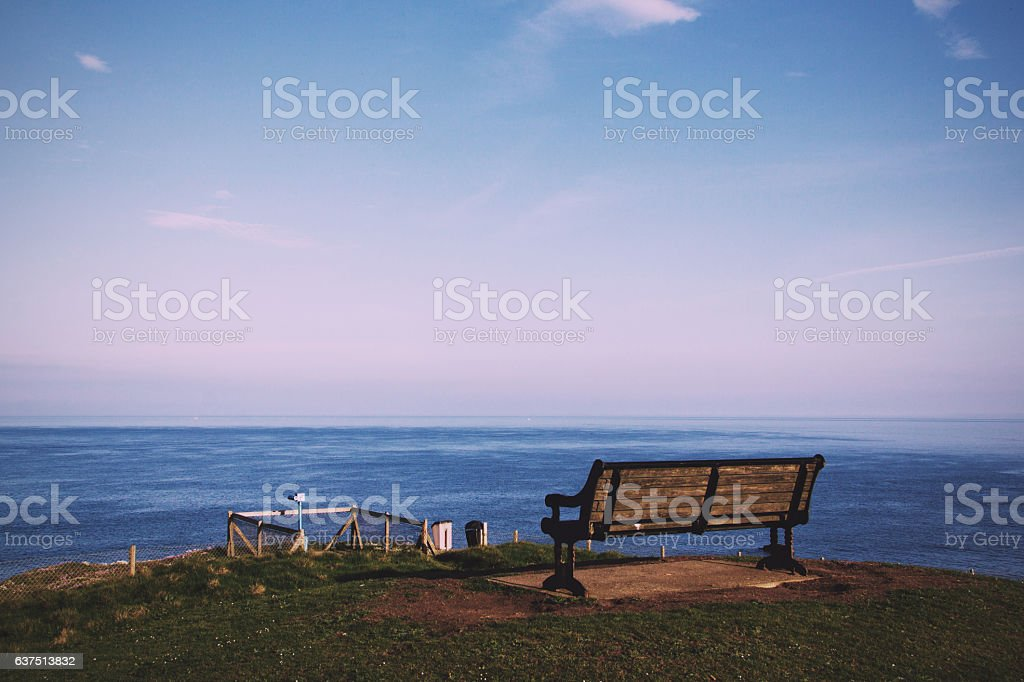Empty bench over looking the coast in Bude, Cornwall Vintage stock photo