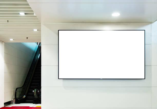 leere plakatwand mit rolltreppe in u-bahn-station - plakatieren stock-fotos und bilder