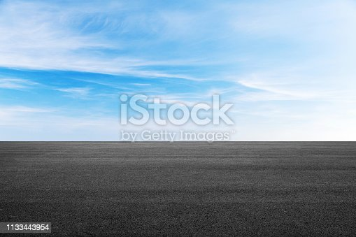 Empty black asphalt road under blue sky with clouds at daytime, background photo texture