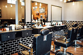 istock Empty black chairs and mirrors in barber shop 1030255416