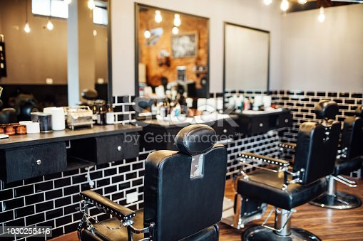 Empty black chairs and mirrors in barber shop. Interior of illuminated hair salon.