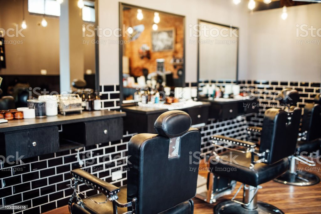 Empty black chairs and mirrors in barber shop stock photo