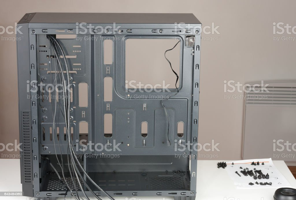 Empty black computer chassis  with screws on table. stock photo