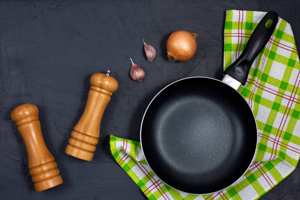Empty black frying pan or skillet with pepper and sea salt stock photo