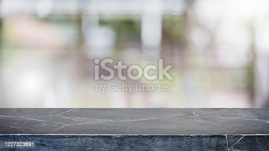 662984994 istock photo Empty black marble stone table top and blur glass window interior restaurant banner mock up abstract background - can used for display or montage your products. 1227323891