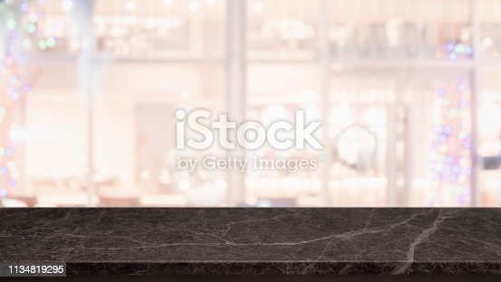 istock Empty black marble stone table top and blurred bokeh cafe and restaurent interior background with vintage filter - can used for display or montage your products. 1134819295
