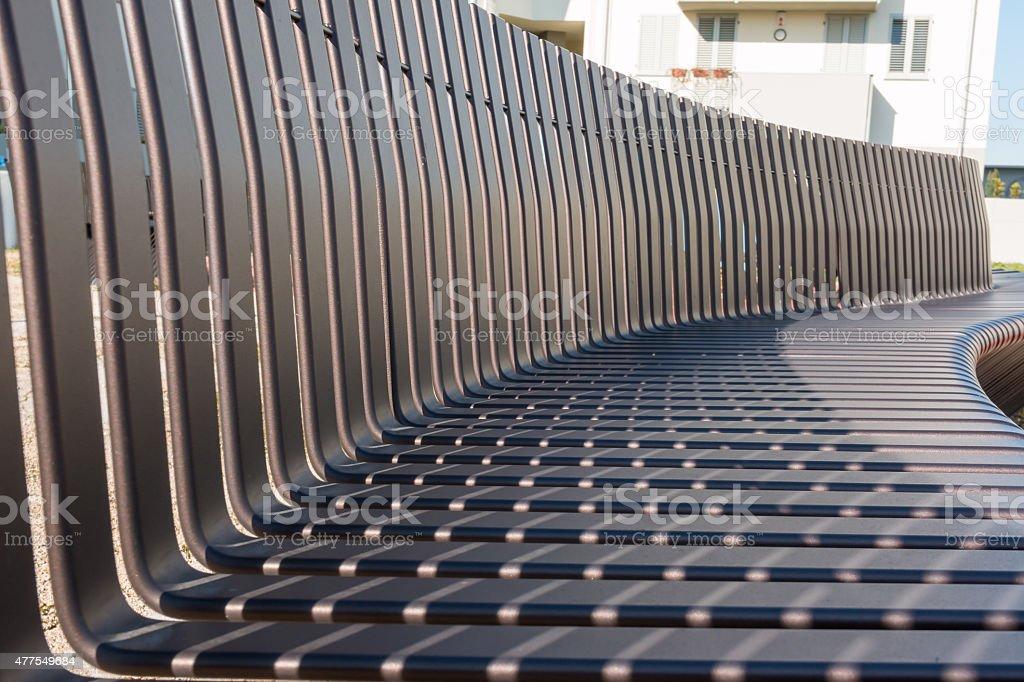Empty black metal bench in public gardens stock photo