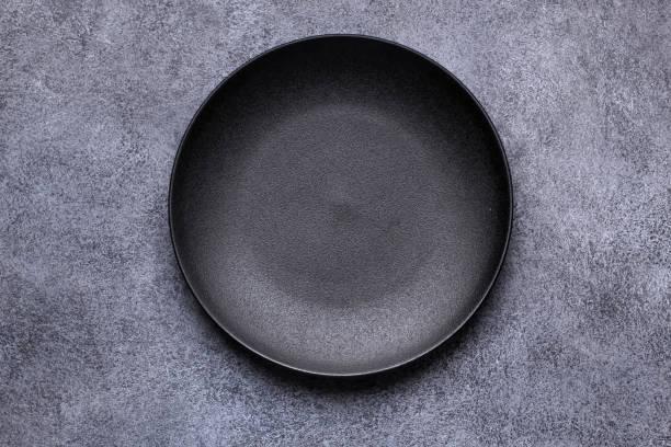 Cтоковое фото Empty black plate on gray