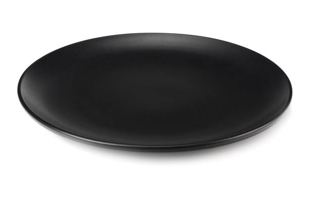 empty black round plate isolated on a white background stock photo