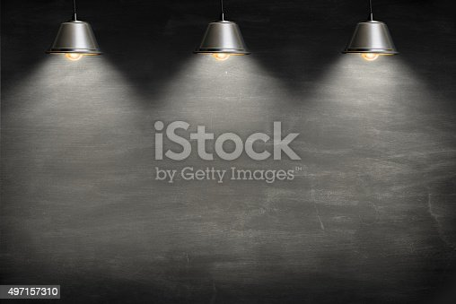 istock Empty blackboard lit from above by 3 suspended lamps. 497157310