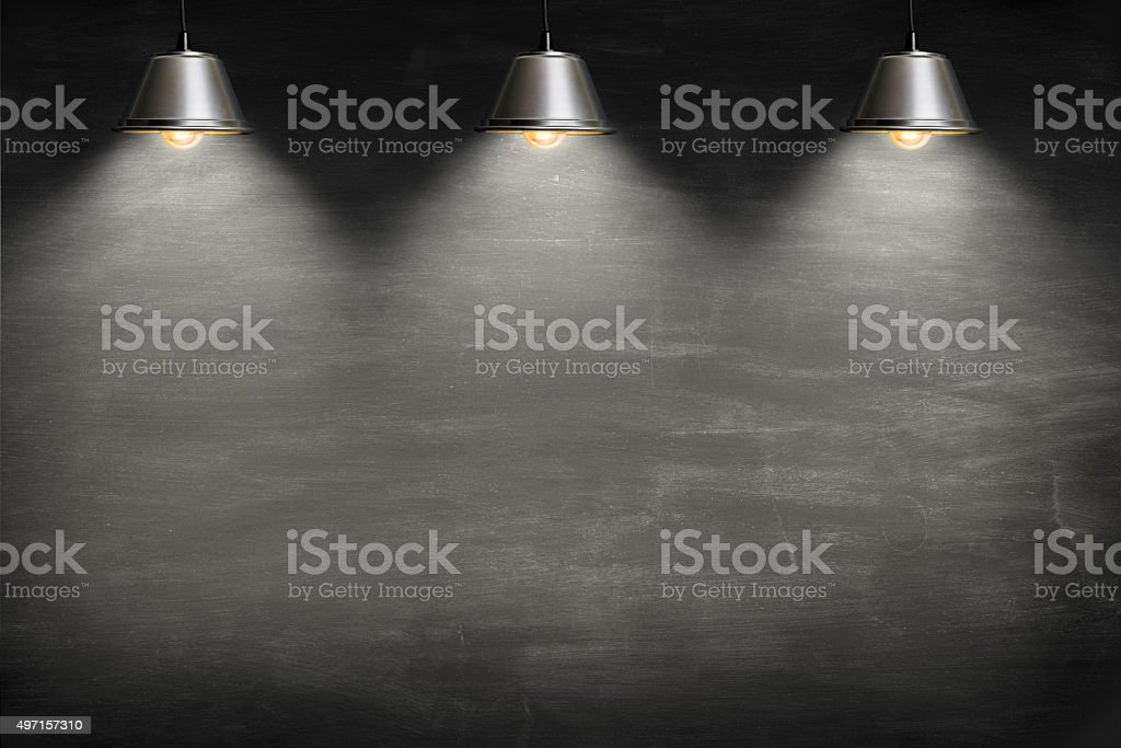 Empty blackboard lit from above by 3 suspended lamps. stock photo
