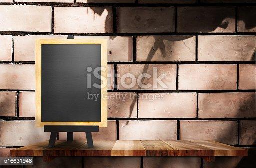 642100994 istock photo Empty blackboard on wooden shelf at brick wall, Mock up 516631946