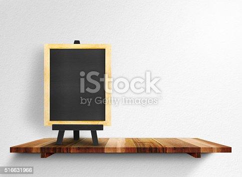 642100994 istock photo Empty blackboard on wooden shelf at white wall, Mock up 516631966