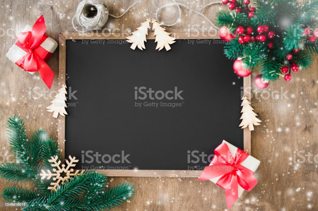 Empty blackboard with christmas decoration, red gift box, fir branches. royalty-free stock photo
