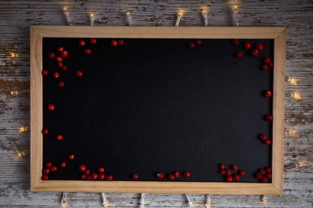 empty blackboard with edges in wood and with small red fruits and lights stock photo