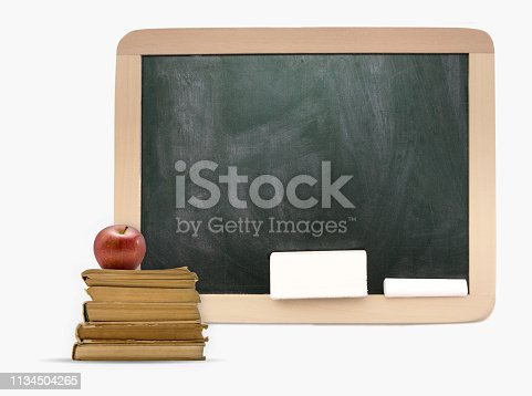 istock Empty blackboard with wooden frame, old books and apple 1134504265