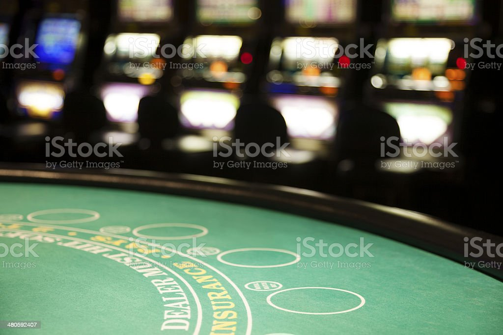 Empty blackjack table and slot machines in a casino stock photo