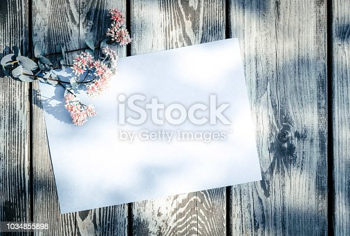 680461500 istock photo Empty, blank greeting card and pink field flowers on aged wooden background in sunlight. Flat lay. Top view with copy space, vintage tone. 1034855898