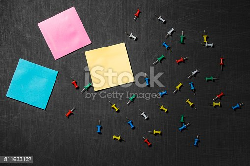 990092558 istock photo Empty blank paper note and thumbtack on black chalkboard background. Mockup. Flat lay. Top view 811633132