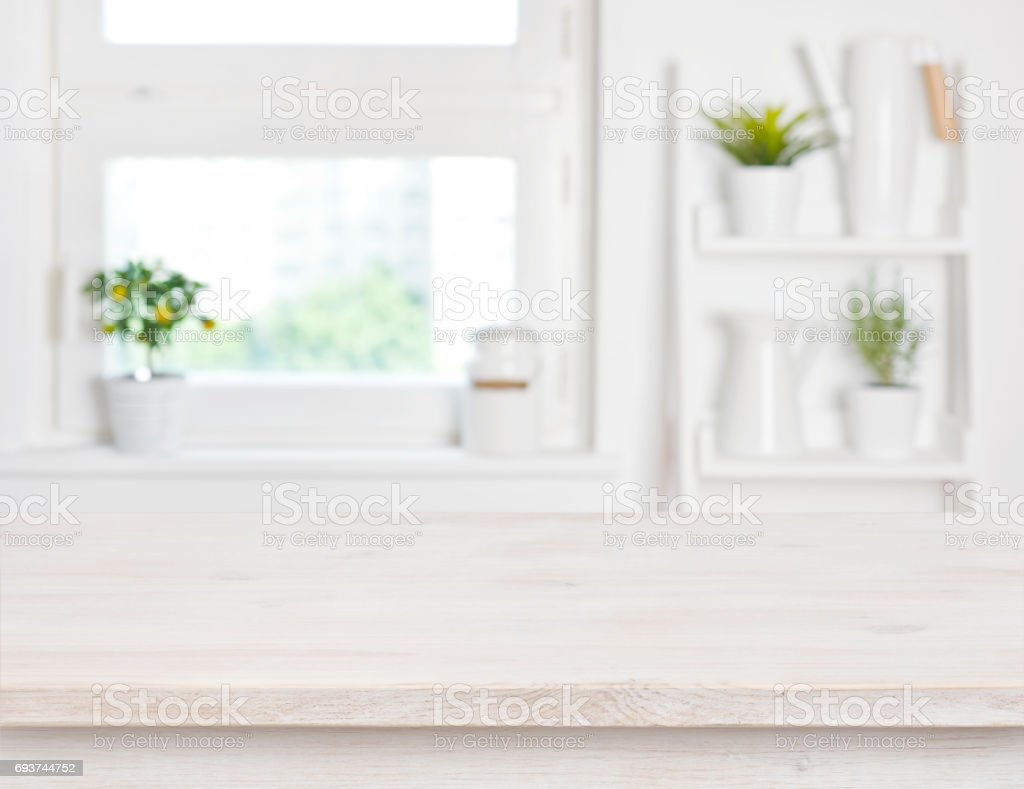 Empty bleached wooden table and kitchen window shelves blurred background stock photo