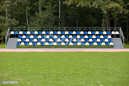 Empty blue and white seats in a footbal or soccer stadium. Grass field and plastic chairs, open door sports arena.