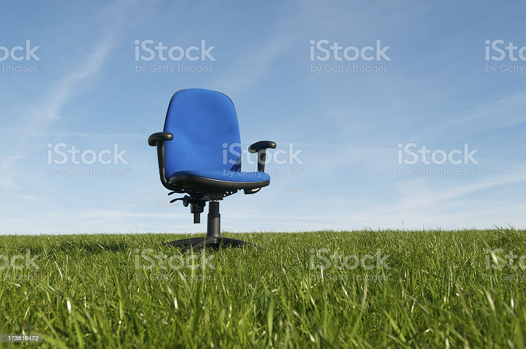 Empty Blue Office Chair Outdoors in Green Grass Meadow Sky royalty-free stock photo