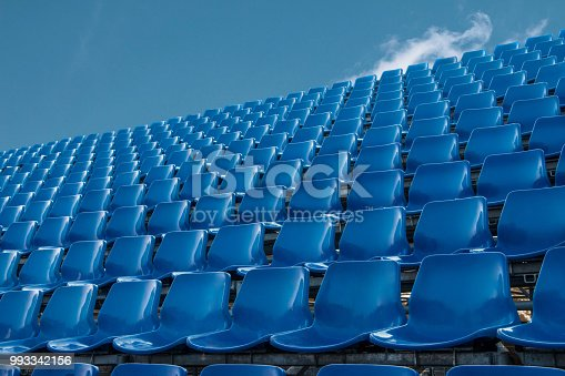 empty blue seat in football stadium with blue sky