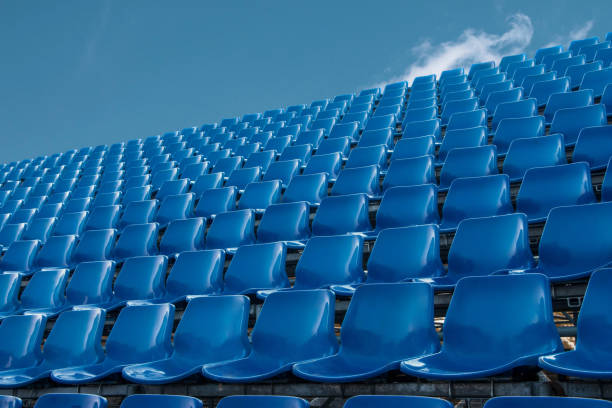 empty blue seat in football stadium with blue sky stock photo