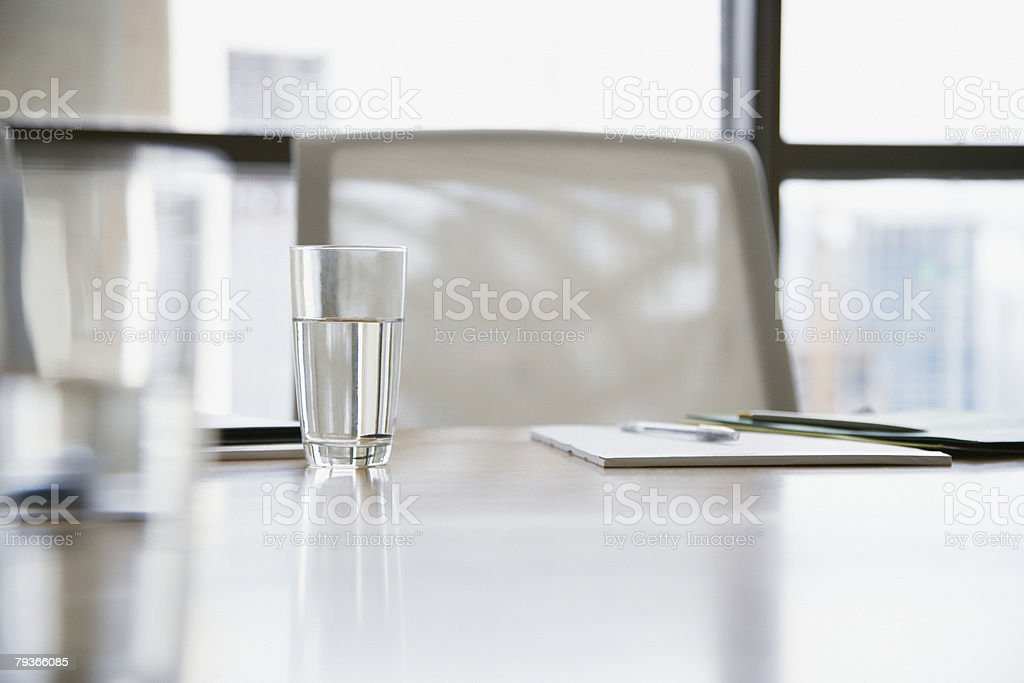 Empty boardroom chair with notepads and glasses of water on table stock photo