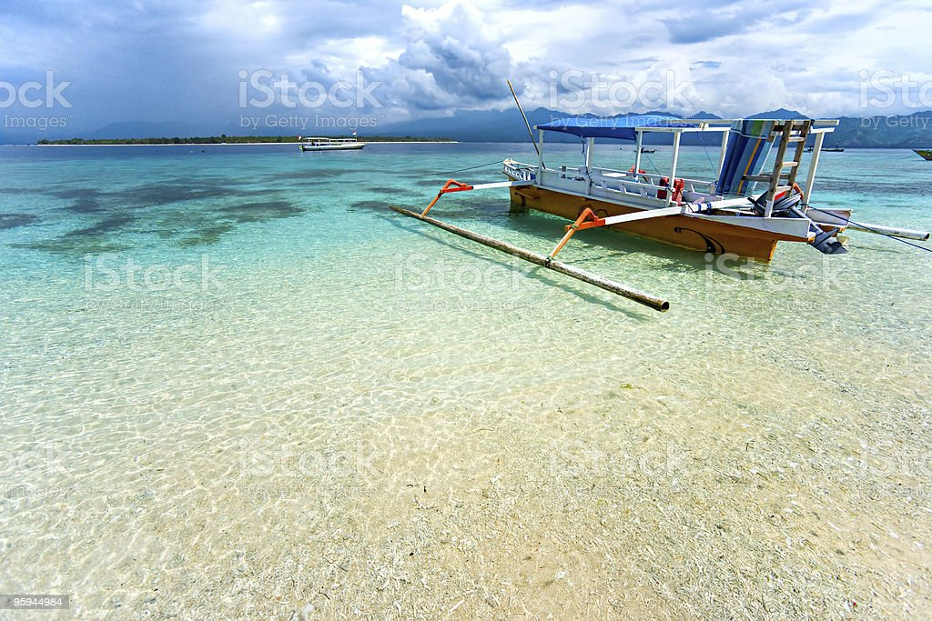 Empty boat in shallow sea waters of Gili Meno, Indonesia stock photo