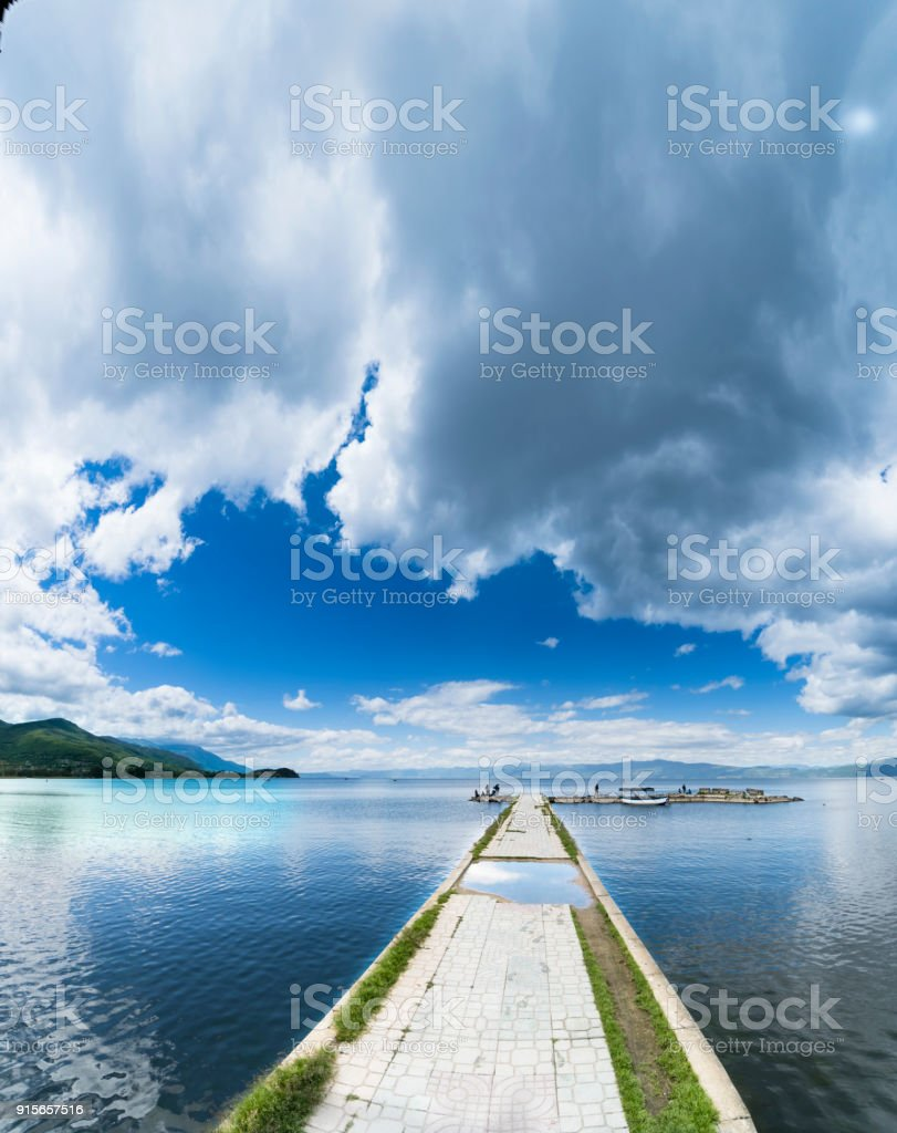 Empty boat port on calm water surface lake in Ohrid, Macedonia, sky copyspace, vertical stock photo