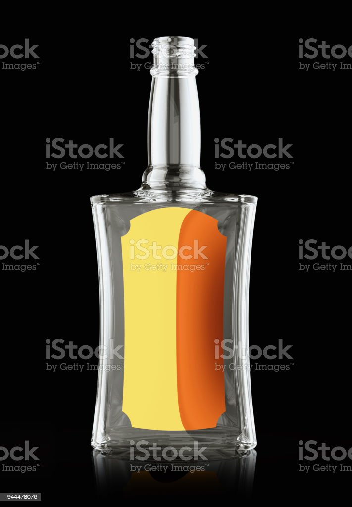 Empty bottle for rum or whisky with golden label on black stock photo