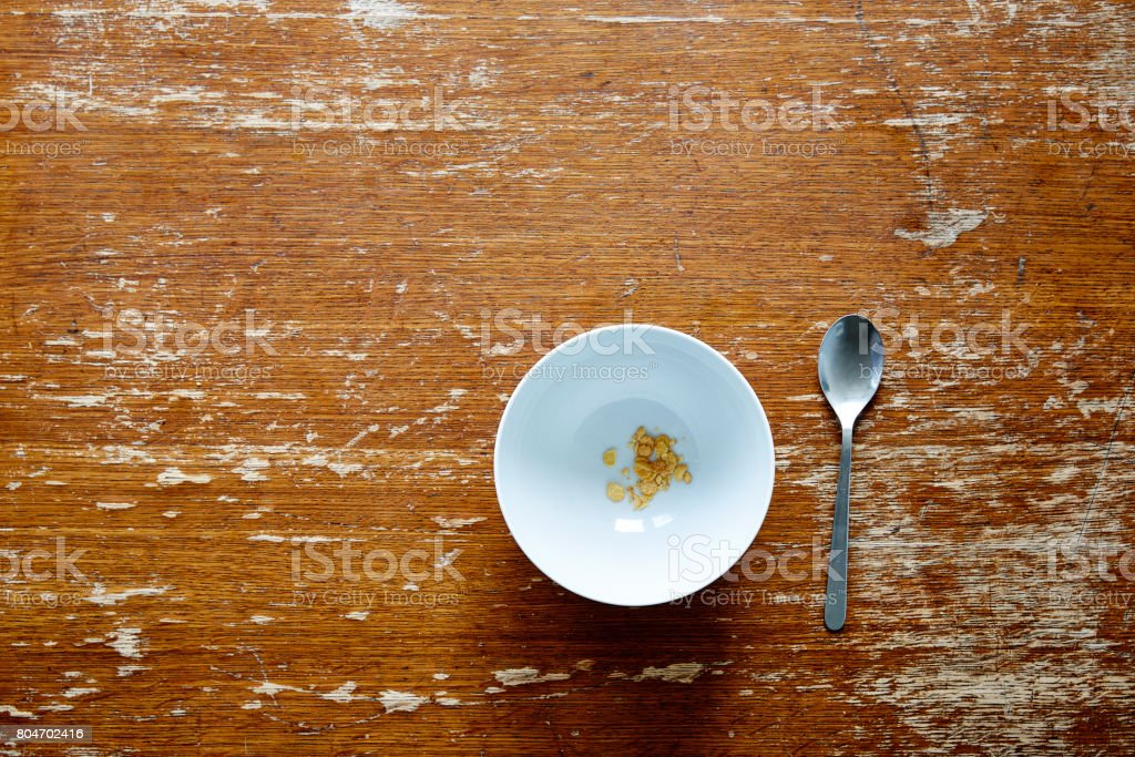 empty bowl with little cereal on dark wooden table stock photo