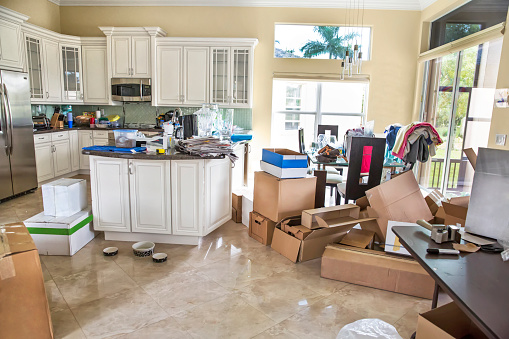 There are many unpacked cartons in the messy kitchen. It looks chaotic in the kitchen with many things on the counters. There are many things that need to packed up in order to move out of a house that has been sold. Taken with a Canon 5D Mark 3.  rm