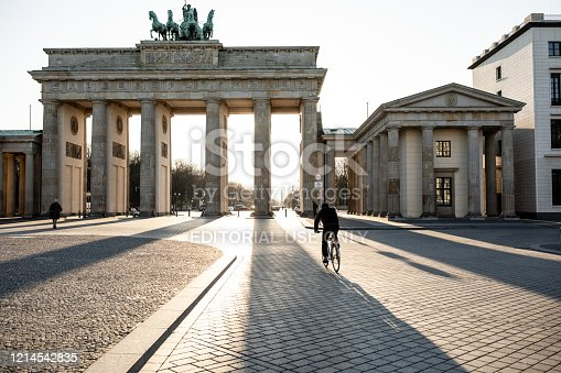 Berlin, Germany - March 23, 2020: Lone biker riding past Berlin's Brandenburg Gate as the city experiences its first day with movement restrictions introducing by the German government to mitigate the spread of COVID-19 Corona-virus