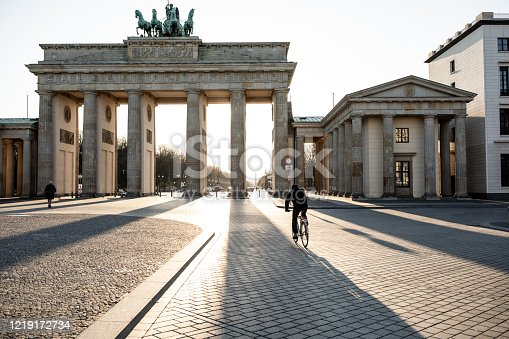 Lone biker riding past Berlin's Brandenburg Gate as the city experiences its first day with movement restrictions introducing by the German government to mitigate the spread of COVID-19 Corona-virus