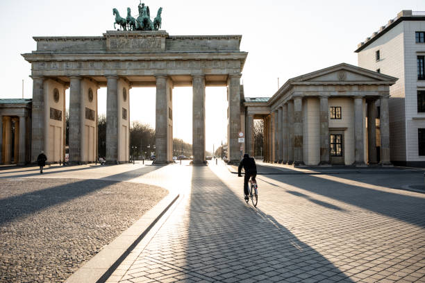 Empty Brandenburg gate during the COVID-19 crisis Lone biker riding past Berlin's Brandenburg Gate as the city experiences its first day with movement restrictions introducing by the German government to mitigate the spread of COVID-19 Corona-virus germany stock pictures, royalty-free photos & images