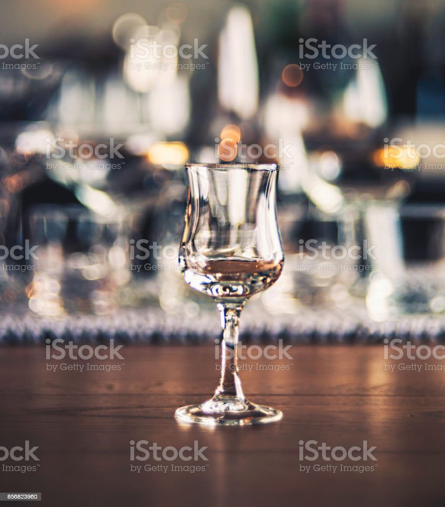 Empty brandy glass with defocused glasses in background stock photo