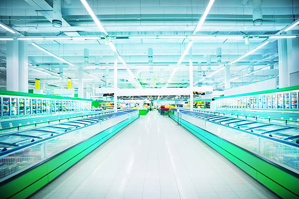 Empty, brightly-lit aisle in large supermarket stock photo