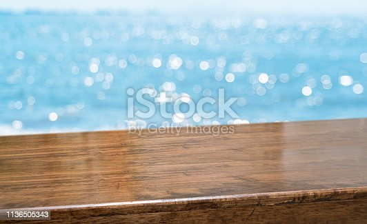 Empty brown glossy wood table top with blur sky and sea boekh background,banner mock up template for display of product