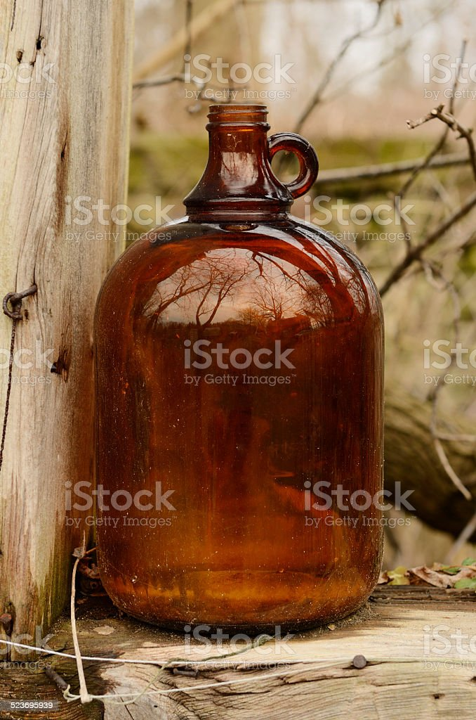 Empty brown moonshine glass jug stock photo